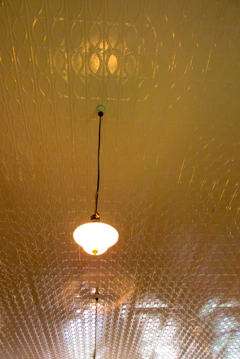 tin ceiling with one of the beautiful light fixtures